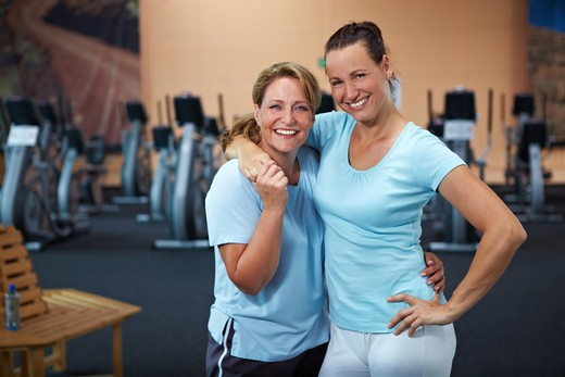 Two happy sporty women standing in a gym : Stock Photo