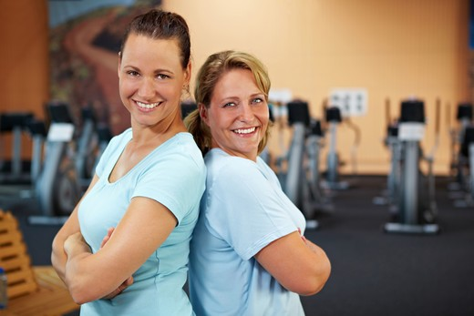 Stock Photo: 4232R-1295 Two happy sporty women standing in a gym