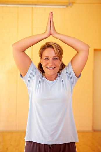 Best Ager woman doing relaxation exercises in a gym : Stock Photo