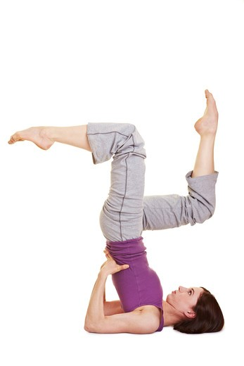 Flexible woman doing aerobics showing a shoulder stand : Stock Photo