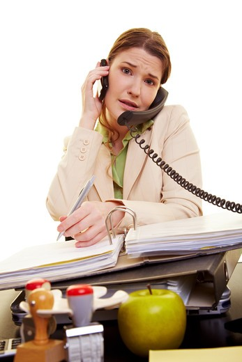 Stock Photo: 4232R-1746 Businesswoman at her desk on the phone taking notes