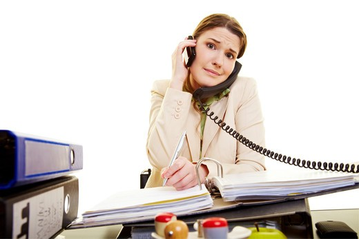Young businesswoman on two phones taking notes : Stock Photo