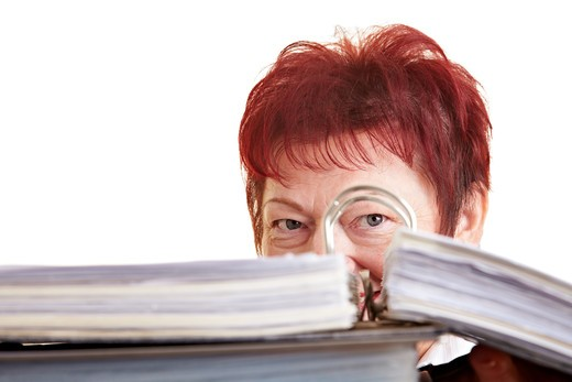 Stock Photo: 4232R-207 Elderly business woman hiding behind her files