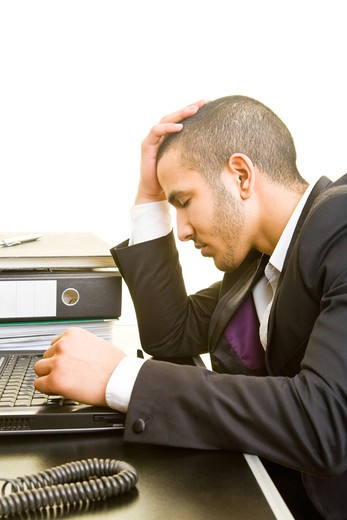 Worried manager at his computer at his desk : Stock Photo