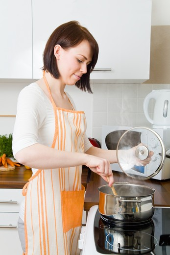 Stock Photo: 4232R-2831 Young woman cooking in her kitchen
