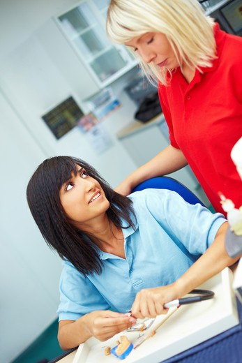 Two female dental technicians talking in laboratory : Stock Photo