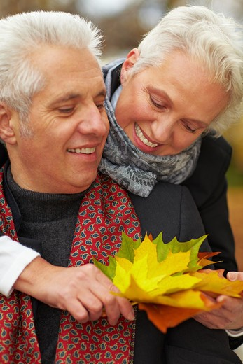 Happy senior couple in an autumn forest : Stock Photo