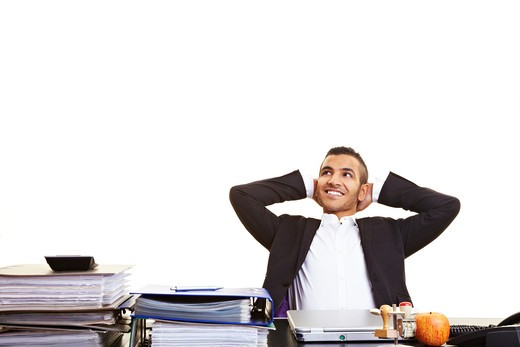 Young moroccan manager leaning back at his desk : Stock Photo