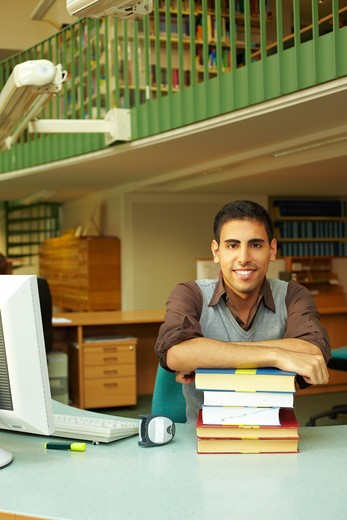 Friendly librarian sitting at desk with books : Stock Photo
