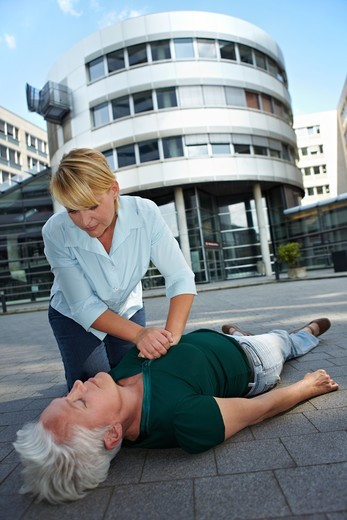Stock Photo: 4232R-4808 Passerby giving CPR to senior woman as First Aid
