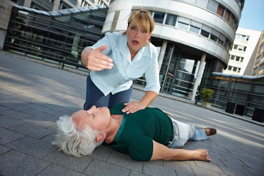 Stock Photo: 4232R-4809 Passerby with unconscious senior woman asking for First Aid help