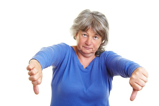 Senior woman pointing with her thumb down : Stock Photo