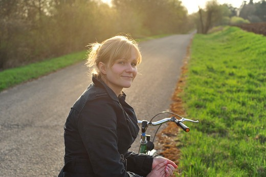 Young woman sitting on bike along bike path : Stock Photo