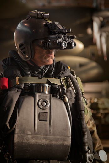 Stock Photo: 4239-1849 U.S. Navy Seal combat diver equipped with night vision prepares for HALO jump operations from a C-130 Hercules.