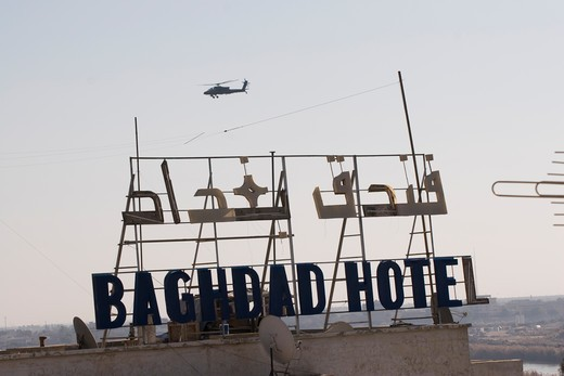 Stock Photo: 4239R-1498 An AH-64 Apache in flight over the Baghdad Hotel in central Baghdad, Iraq