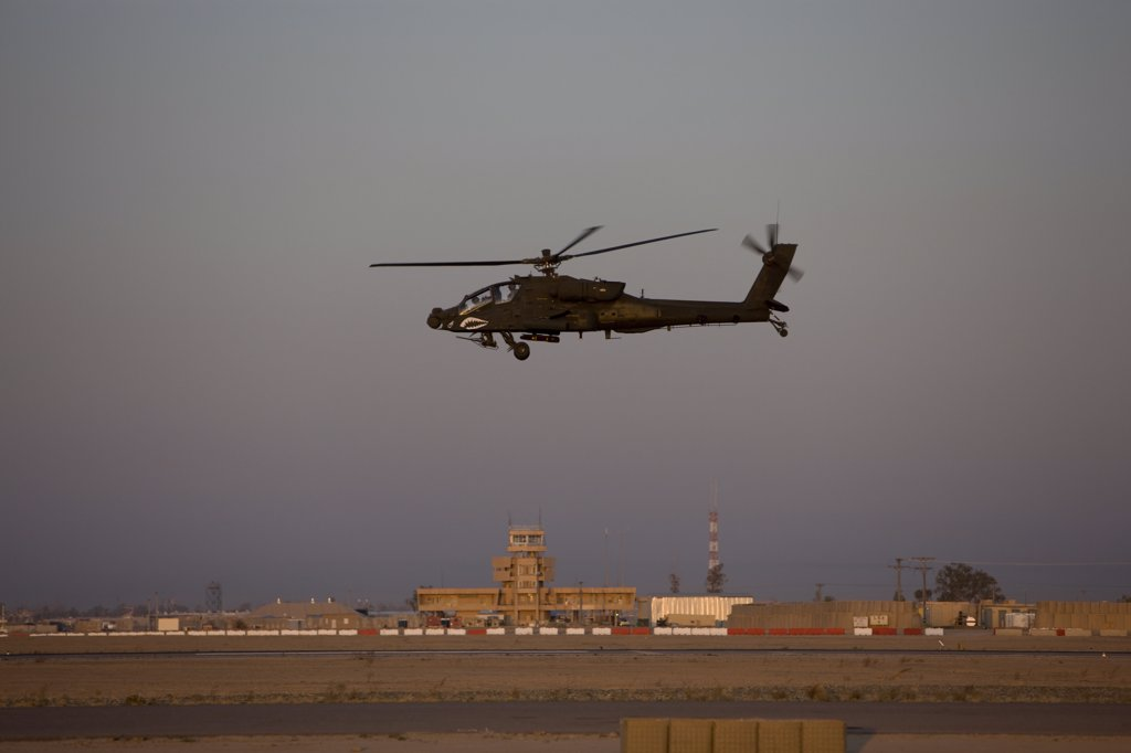 Stock Photo: 4239R-1572 Tikrit, Iraq - An AH-64D Apache Longbow Block III attack helicopter flies by the control tower on Camp Speicher