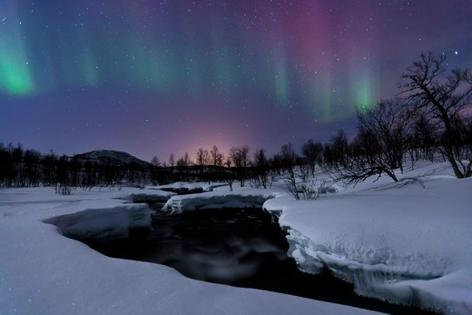 Stock Photo: 4239R-1927 Aurora Borealis over Blafjellelva RIver in Troms County, Norway. Auroras are the result of the emissions of photons in the Earth's upper atmosphere.