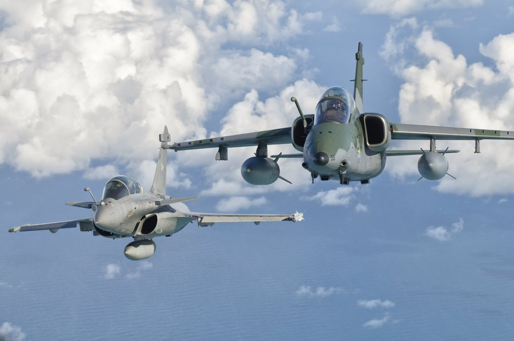 A Dassault Rafale of the French Air Force flys alongside an Embraer A-1B of the Brazilian Air Force during Cruzeiro Do Sul (CRUZEX) in Brazil. CRUZEX V is a multinational exercise encompassing real means from the Air Forces of Argentina, Brazil, Chile, France, Uruguay, United States, Venezuela and simulated means from Land and Maritime Components that takes place October 28th to November 19th, 2010, on the Northeast coast of Brazil. : Stock Photo