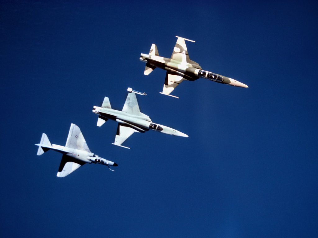 Stock Photo: 4239R-3648 Three TOPGUN fighters from the Navy Fighter Weapons School zoom above the Pacific during a training mission. Top to bottom: F-5F Tiger II, F-5E Tiger II, and A-4E Skyhawk.