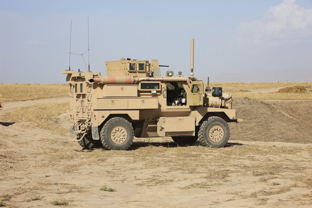 Stock Photo: 4239R-3922 A U.S. Army Cougar MRAP vehicle parked overlooking the top of a wadi during a weapons familiarization shoot, Kunduz, Afghanistan