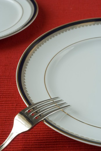 fork and porcelain plates in a perspective over red (selective and soft focus) : Stock Photo