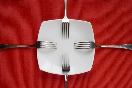 Stock Photo: 4240R-2493 four forks and porcelain plate over red