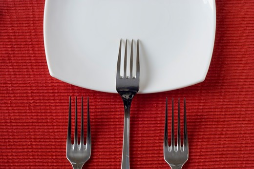 three forks and porcelain plates in a perspective over red (selective and soft focus) : Stock Photo