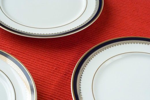 Stock Photo: 4240R-2513 porcelain plates in a perspective over red (selective and soft focus)