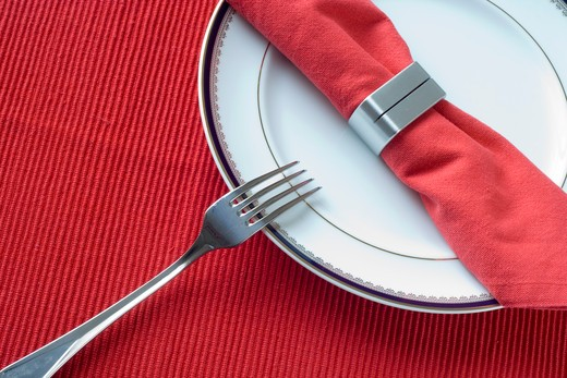 Stock Photo: 4240R-2515 a red napkin on a china plate (selective focus)