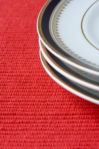 Stock Photo: 4240R-2529 porcelain plates in a perspective over red (selective and soft focus)