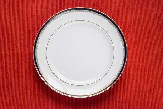 lonely porcelain plate over red (copy space in the plate) : Stock Photo