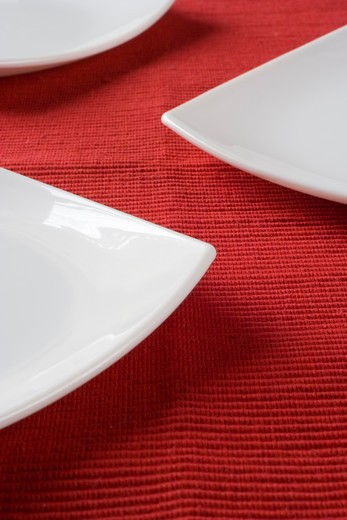 Stock Photo: 4240R-2540 porcelain plates in a perspective over red (selective and soft focus)