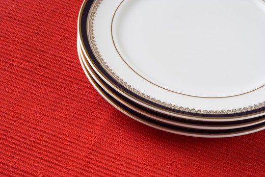 porcelain plates in a perspective over red (selective and soft focus) : Stock Photo