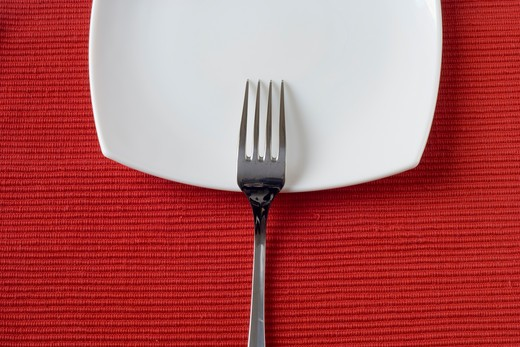 Stock Photo: 4240R-2550 fork and porcelain plate over red (copy space in the plate)