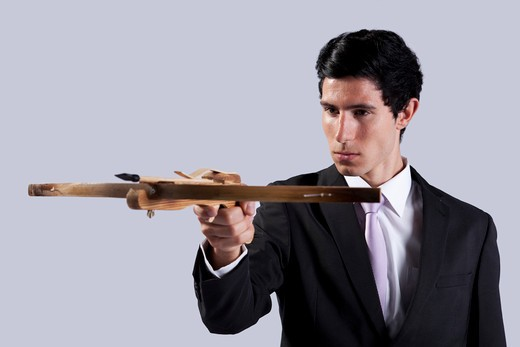 Modern businessman aiming with a crossbow (isolated on gray) : Stock Photo