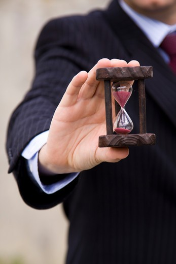 Stock Photo: 4240R-2898 a businessman showing how to save time (selective and soft focus)