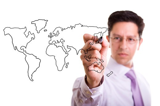 Stock Photo: 4240R-4847 businessman drawing the world map in a whiteboard (selective focus)