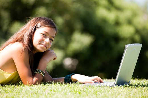 little girl studing with her laptop at the park : Stock Photo