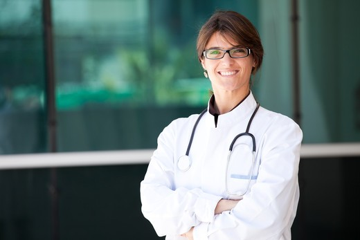 Friendly female doctor smiling to you next to a clinic : Stock Photo