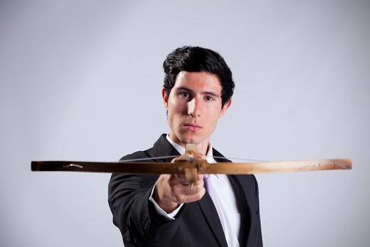 Modern businessman aiming with a crossbow : Stock Photo