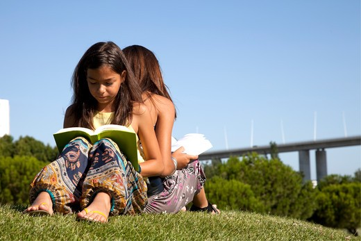 two young sisters reading books at the park : Stock Photo