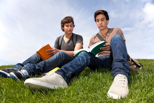 two young student reading books at the school park : Stock Photo