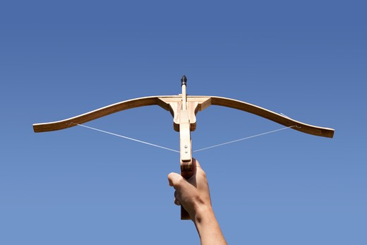 Hand holding a crossbow aiming to the sky : Stock Photo
