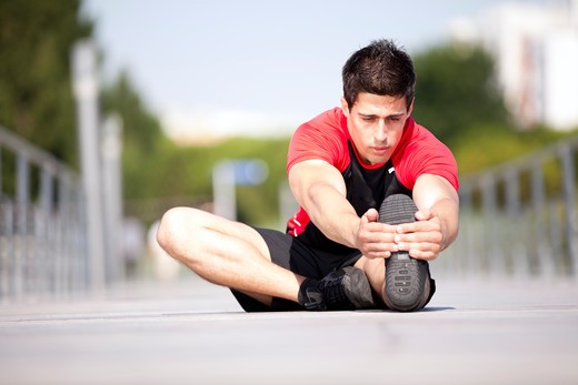 Stock Photo: 4240R-7363 Athlete at the city park warming and stretching
