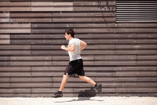 Men athlete running next to some city wall : Stock Photo