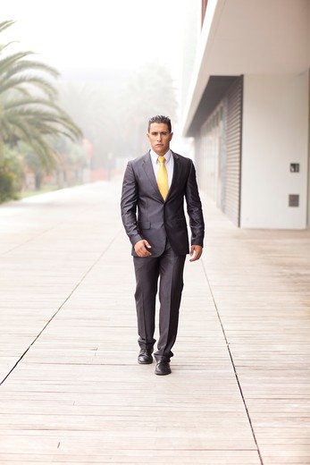 Confident businessman walking next to his office building : Stock Photo