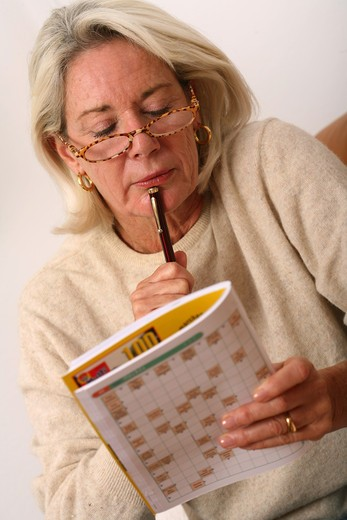 Stock Photo: 4252-10012 Senior woman crosswords