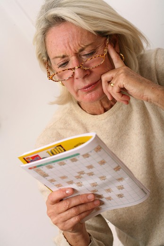 Stock Photo: 4252-10013 Senior woman crosswords
