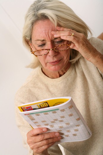 Stock Photo: 4252-10014 Senior woman crosswords