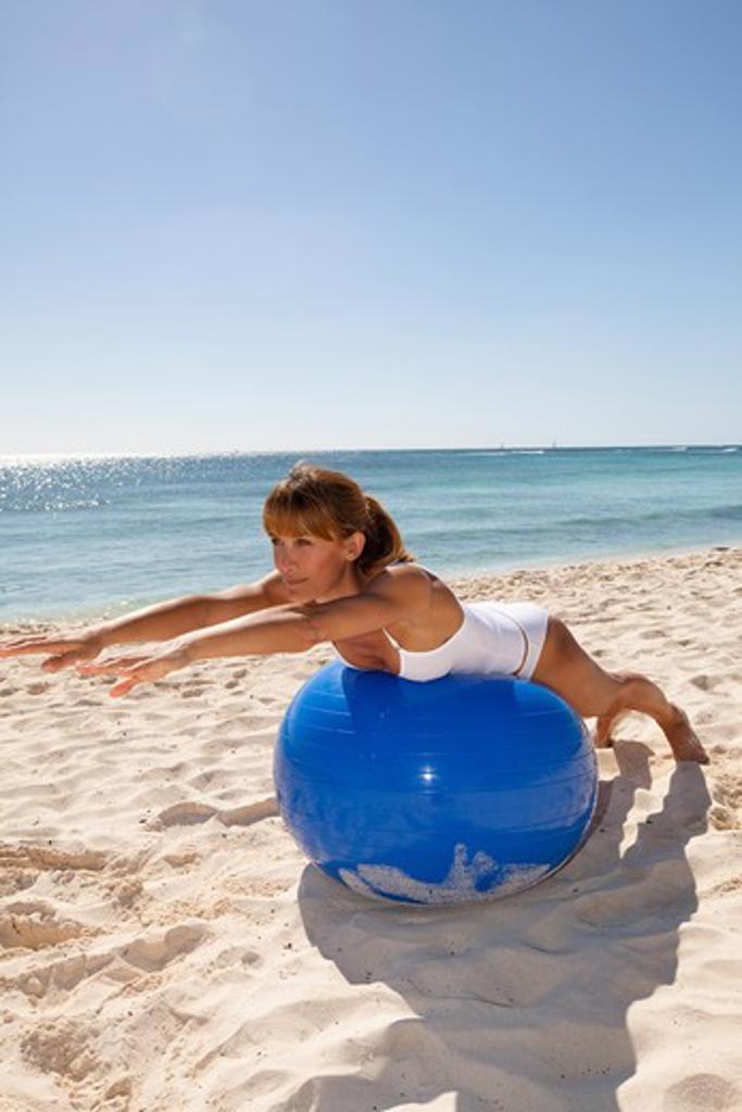 Stock Photo: 4252-19576 Woman streching ball beach